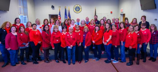 Town Supervisor Angie Carpenter and 50 of Town of Islip employees pose for a photo, wearing read in support of the movement.