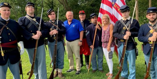 Town Council Members Cochrane and Mullen stand with Town Historian Munkenback and members of the reenactment group on green lawns infront of an american flag.