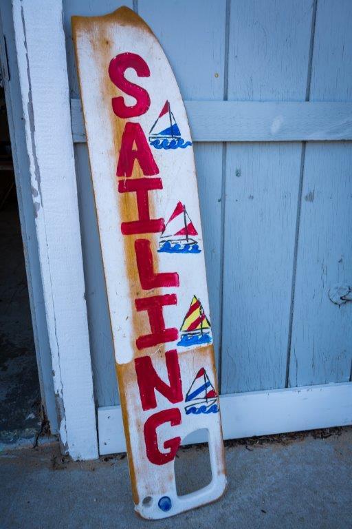 A sign with the word Sailing written vertically, 3 sail boats painted on it.